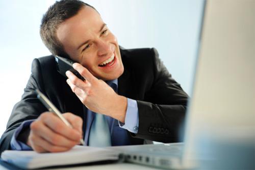 молодой человек улыбаясь разговаривает по телефону и записывает