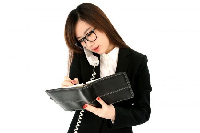 Девушка разговаривает по телефону и держит блокнот