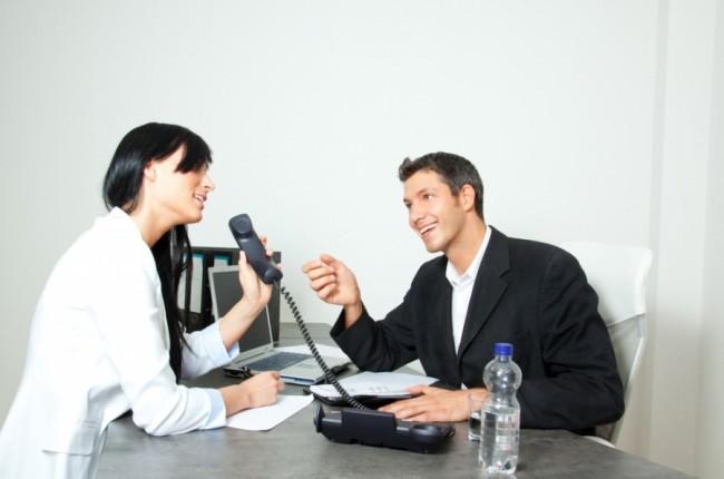 девушка держит телефонную трубку и смотрит на мужчину