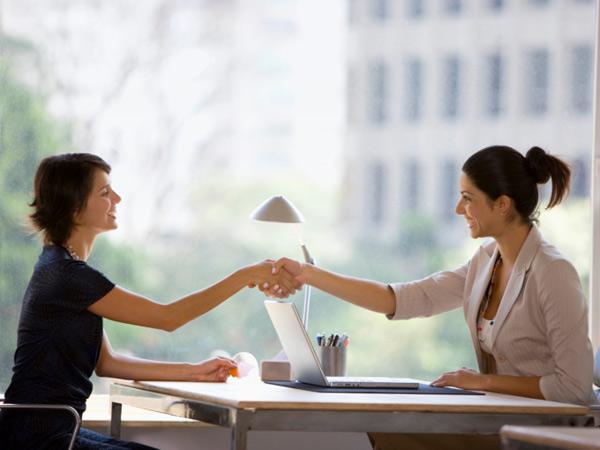 2 женщины за столом напротив окна, пожимают руг другу руки