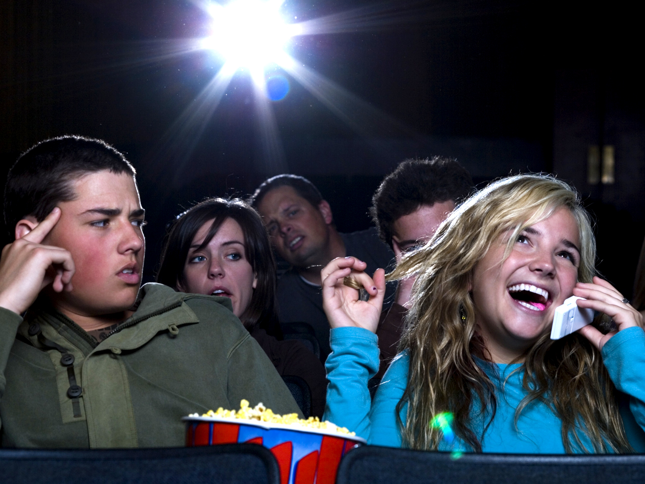 Девушка говорит по телефону в кинотеатре