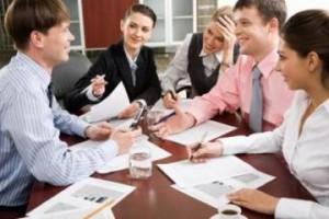 деловые люди сидят за столом с бумагами и ручками в руках