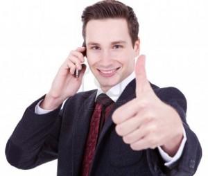 Молодой человек показывает большой палец, разговаривая по телефону