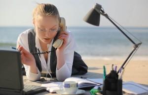 девушка на пляже с телефоном и ноутбуком, работает