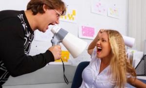 женщина кричит в рупор на молодую девушку