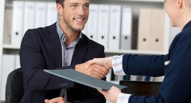 молодого человека принимают на работу и пожимают руку