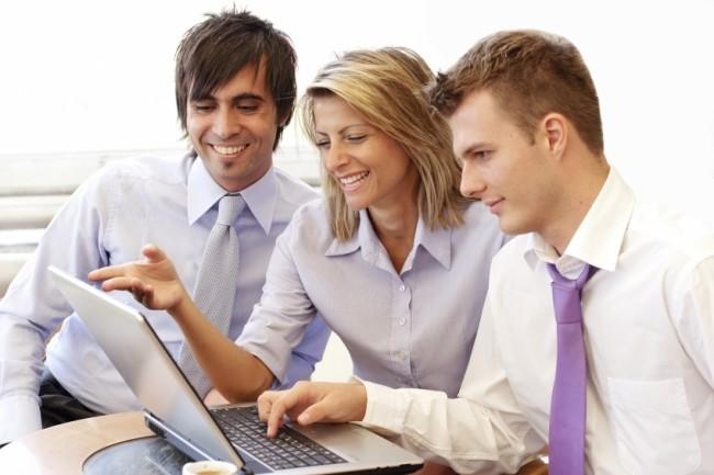 Работники смотрят в компьютер и улыбаются