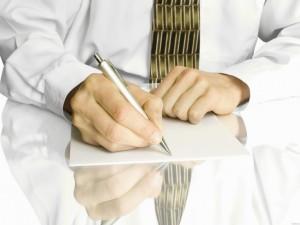 руки клерка, собравшегося писать заявление на чистом листе бумаги