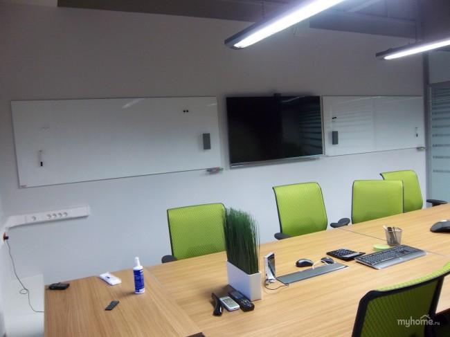 пустой кабинет с большим столом для совещаний, зелеными стульями и досками на всю стену