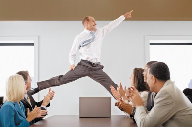 офисный работник подпрыгнул над столом коллег, коллеги аплодируют