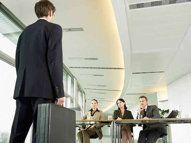 собеседование: соискатель спиной с дипломатом в руке, за столом 3 рекрутера