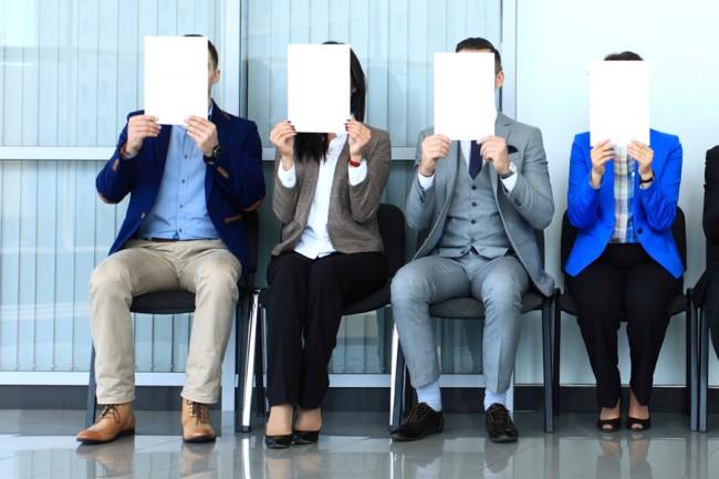 4 человека на стульях, с лицами, закрытыми белыми листами
