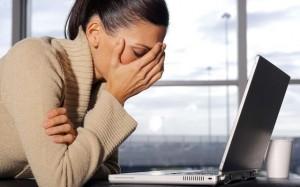 фото усталой девушки, с рукой у лица, за ноутбуком
