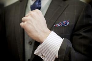 рука в рубашке с запонкой-стрекозой, клетчатый иджак и платочек