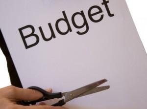 режем ножницами лист с надписью бюджет