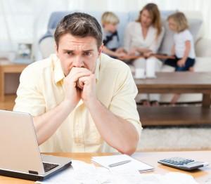 не первом плане мужчина у ноутбука, задумчивый, на втором - его семья: жена, дети
