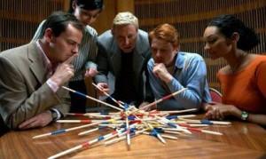 5 человек над столом смотрят на ворох палочек