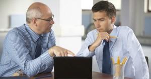 Начальник за столом вместе с работником обсуждают вопрос