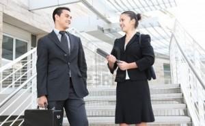 Мужчина и женщина в деловых костюмах искренне друг другу улыбаются